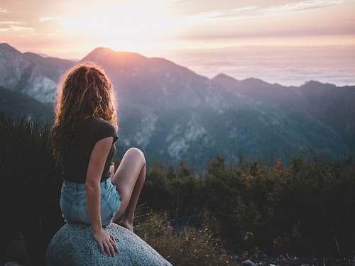 person woman sitting on rock human