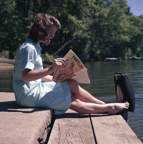 person woman sitting while reading near body of water vintage