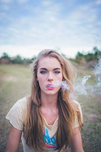 person woman smoking while sitting on green grass human
