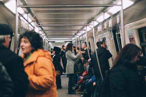 person woman standing inside train surrounded by people subway