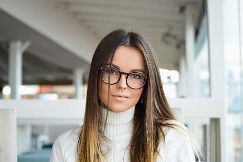 human woman standing near glass window glasses