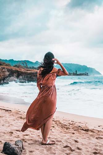 person woman standing on brown sand sand