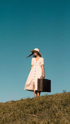person woman standing on green grass holding brown leather suitcase wearing white button-up dress human