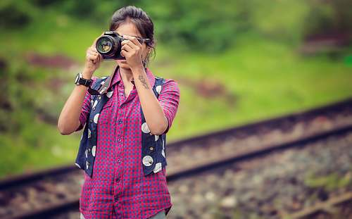 person woman taking photo in selective focus photography human