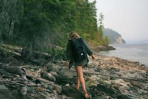 human woman walking on rocky seashore person