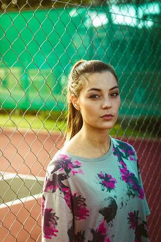 woman woman wearing floral top beside chain link fence during day female