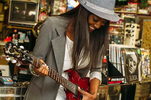 woman woman wearing grey suit jacket playing brown telecaster guitar near assorted poster lot music