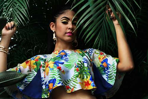 woman woman wearing multicolored floral crop-top holding green palm leaves fashion