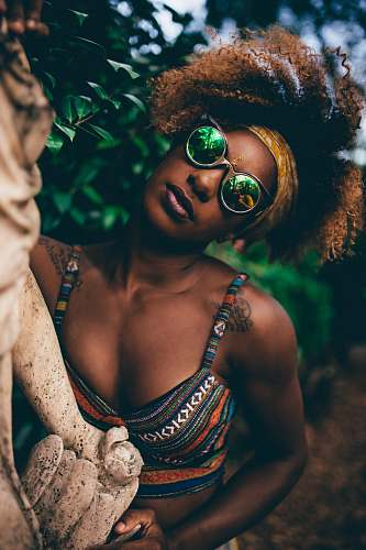 person woman wearing round sunglasses holding statue near tree close-up photography human