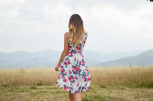 woman woman wearing white, purple, and pink floral dress standing near brown leaf grass field during daytime girl