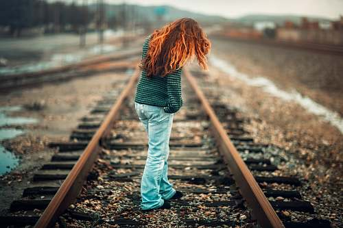 human woman with orange hair wearing black and gray stripe long-sleeve shirt and light-blue denim pants standing on train rail at day train track