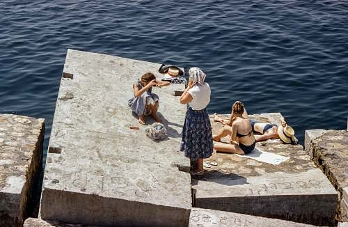 person Women in swimsuits and vintage clothing sunbathing on cement cubes by the sea human