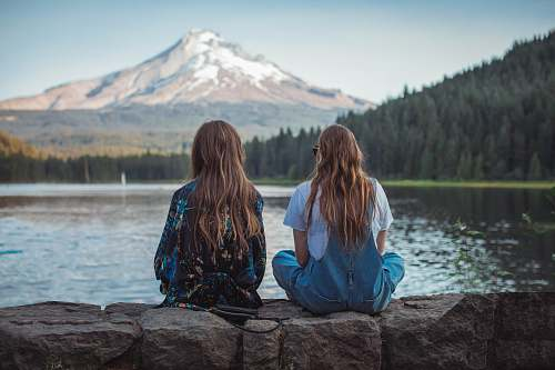 person women sitting on rock near body of water human
