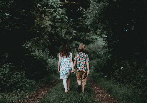people boy and girl walking hand in hand towards the woods kid