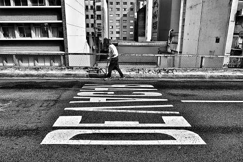 people gray scale photography of person walking beside pave road black-and-white