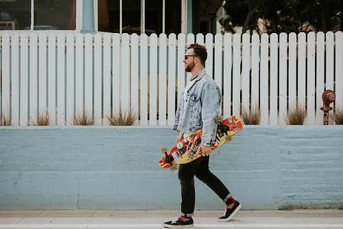 people man carrying long board walking beside white fence skateboard