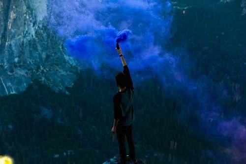 people man holding blue powder while raising hand smoke