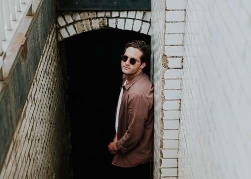 people man leaning on beige wall near hallway human