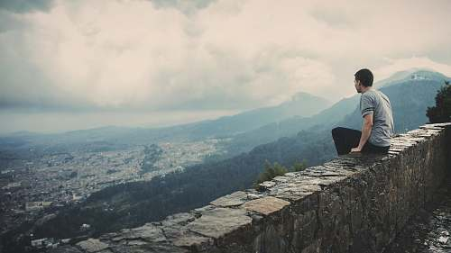 people man sitting alone on concrete brick wall facing mountain and city under cloudy sky human