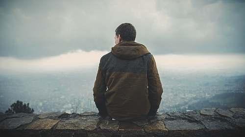 people man sitting on brown concrete surface while staring sideway human