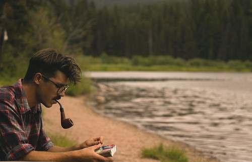 people man smoking on pipe beside lake human
