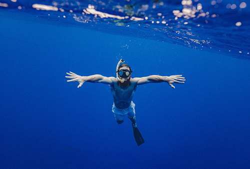 people man snorkling underwater blue