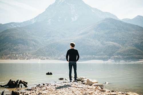 people man standing on front of lake at daytime lake