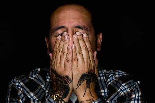 people man wearing black, white, and gray plaid sport shirt covering his face tattoo