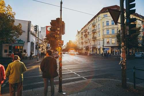 people men walking near concrete buildings intersection
