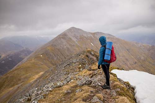 mountain person at peak of mountain carrying red backpack nature