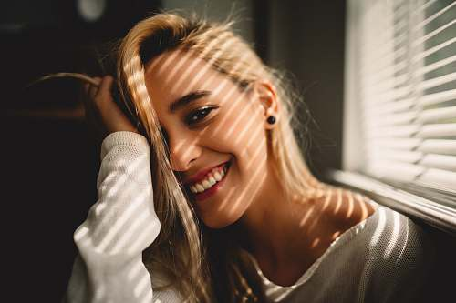 people selective focus photography of smiling woman holding her hair beside window blinds woman