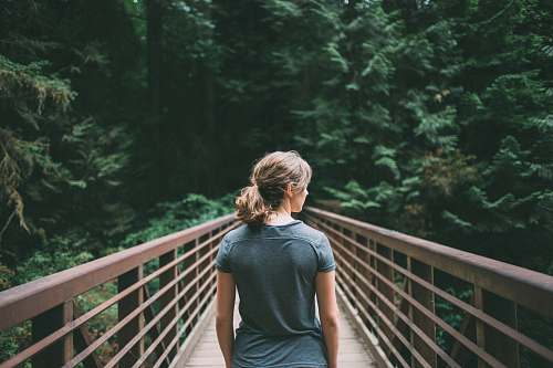 people selective focus photography of woman in black t-shirt standing on bridge woman