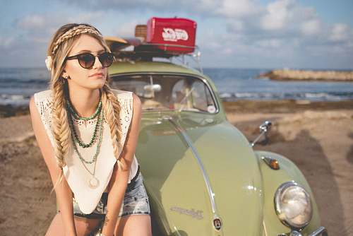 people selective focus photography of woman sitting on Volkswagen Beetle parked on beach shore girl
