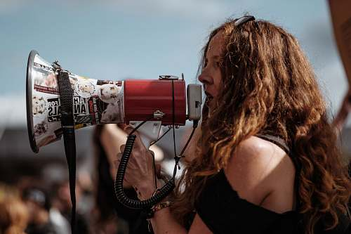 people selective focus photography of woman wearing black cold-shoulder shirt using megaphone during daytime human