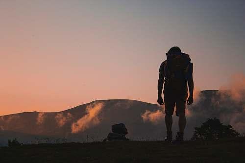 people silhouette of man walking along field leading to mountain human