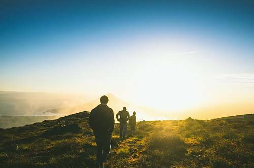 people silhouette of three men falling in line while walking during golden hour hiking