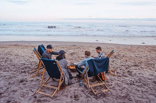 people three men and one woman sitting on beach lounge in front fire pit near seashore human