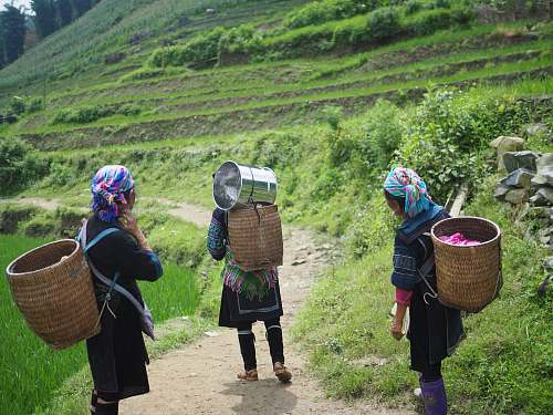 people three people wearing brown wicker baskets walking on road human