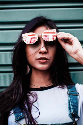 people woman holding sunglasses near gray walpl human