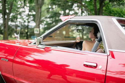 people woman riding on red coupe automobile