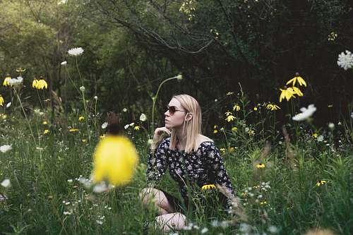 blonde woman sitting on grass field surrounded with flowers while hand on chin woman