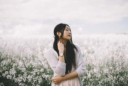 people woman wearing peach inner top with gray knitted cardigan standing behind white flowerfield during daytime photography woman