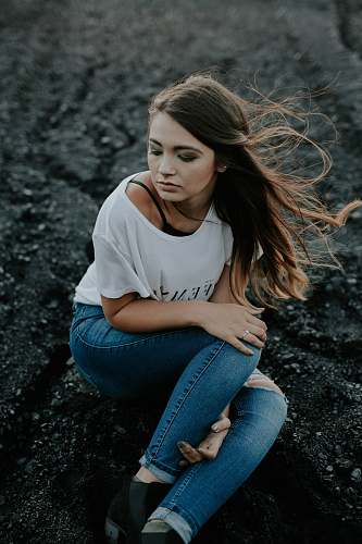 people woman wearing scoop-neck shirt and distressed jeans sitting on ground while holding knee human