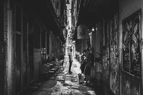 city grayscale photo of people in between of white concrete structures alley