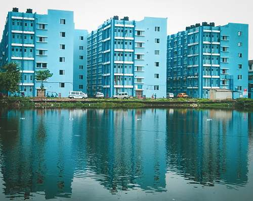 city blue painted buildings beside body of water high rise