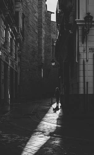 city grayscale photo of person standing in between buildings black-and-white