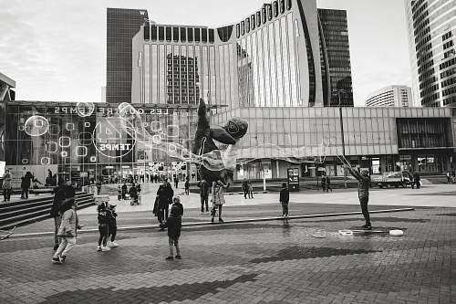 city grayscale photography of person making bubbles black-and-white
