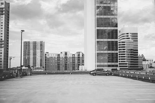 city grayscale photography of vehicle parking with high-rise building background black-and-white