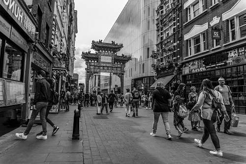 downtown greyscale photography of people walking on street between buildings black-and-white