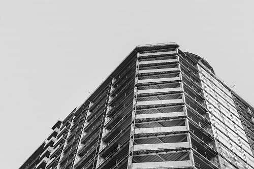 city low-angle grayscale photography of concrete building during daytime black-and-white